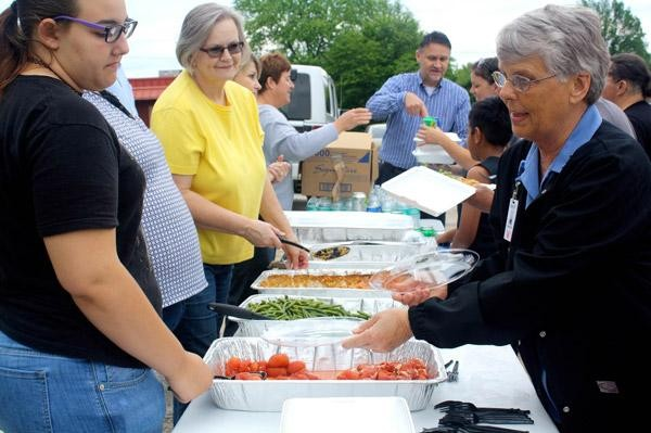 Sister Anita DeSalvo, RSM, (right) and other Mercy volunteers prepare plates of food May 26 to serve to people who live at 8th Street Motel in Rogers. (Courtesy: Arkansas Catholic)