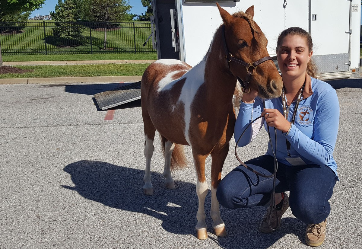 AppleJack poses with Emily Hoffman, founder of AppleJack Therapy, before visiting Mercy Kids.