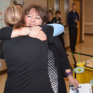 Venus Fuchs hugs nurse Christina Terrell, RN, after reading the nomination form she submitted for the DAISY Award for Extraordinary Nurses.