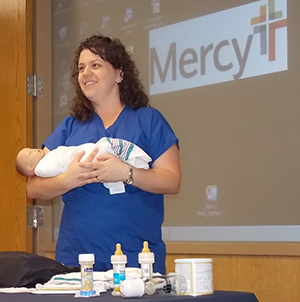 Amy Schwent, RN, demonstrates proper techniques for holding an infant during the seminar.