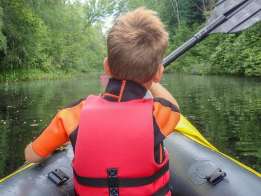 kid-behind-paddling-boat-lake-