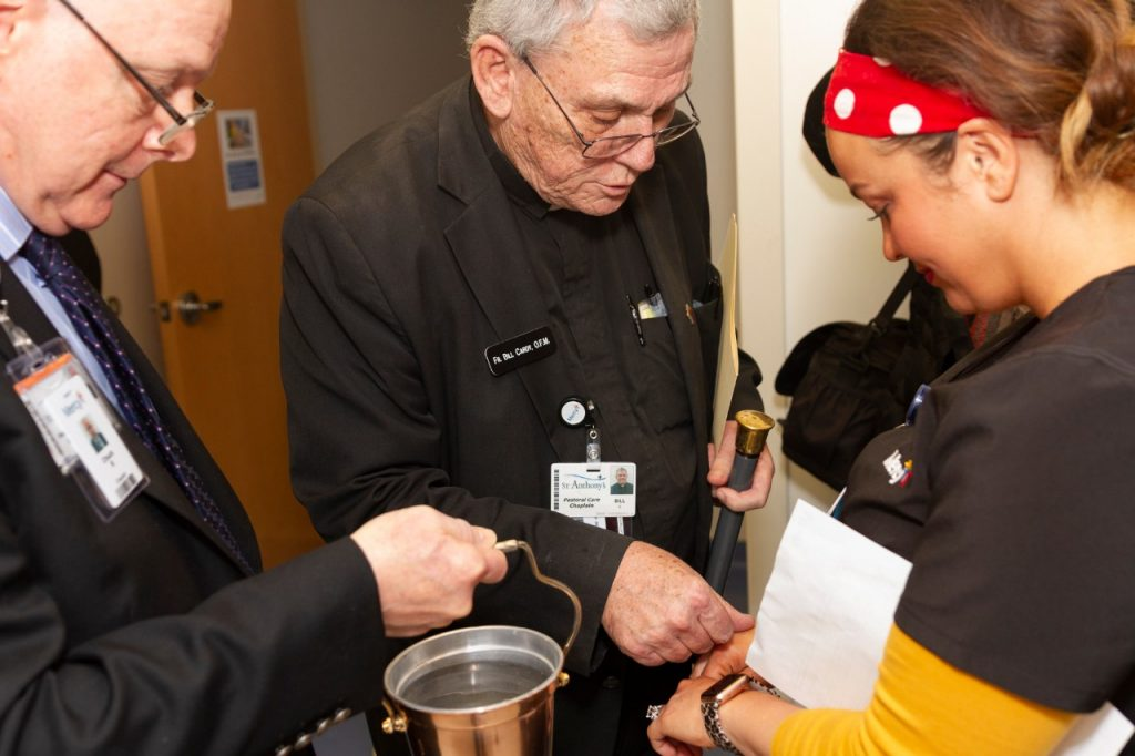 Father Bill Cardy, OFM, Mercy Hospital South Chaplain, blesses the hands of a co-worker in the Mercy Kids ER.