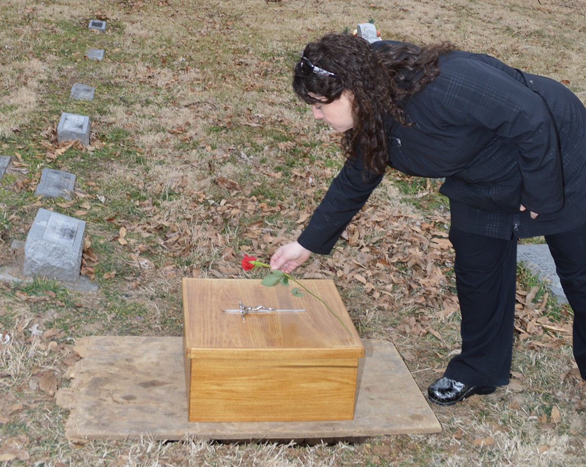 Mother/Baby Unit nurse clinician Amy Schwent places a rose on the casket prior to the burial.