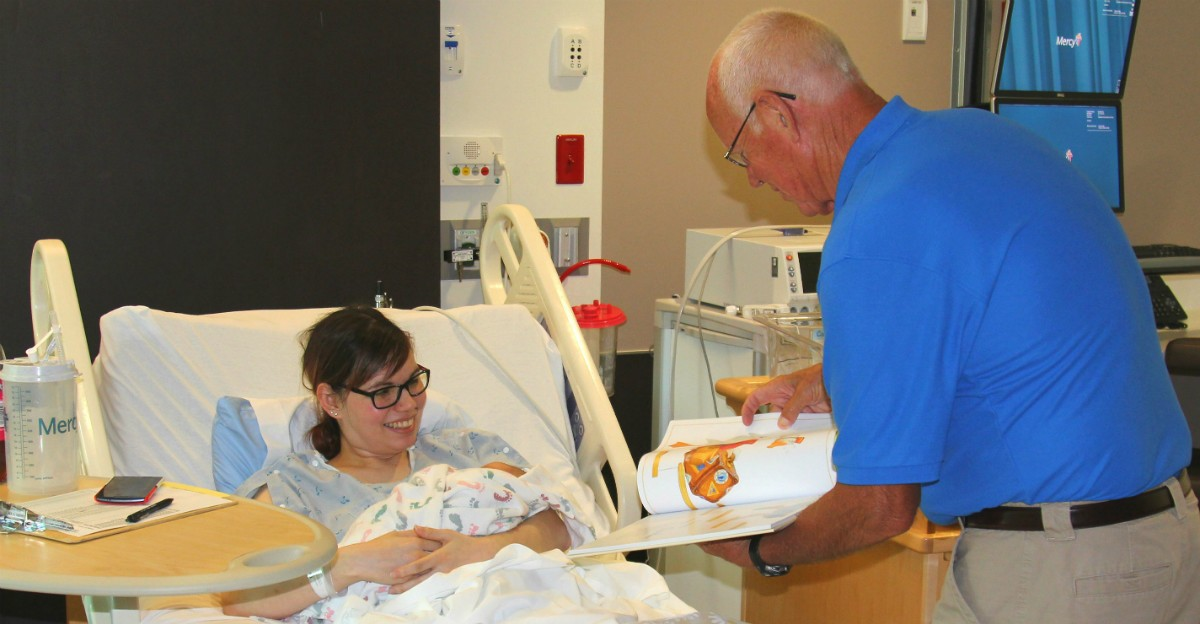 Larry Hartman of the Carthage Family Literacy Council presents a Mother Goose nursery rhyme book recently to Carthage's Megan Lindsey, who holds her 12-hour-old son, Kylo, in the Mercy Hospital Joplin Birthing Center.