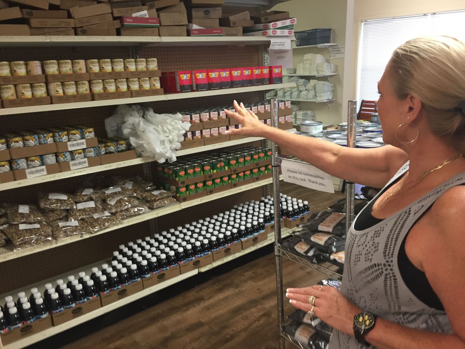 A volunteer looks over the Society of St. Vincent de Paul's food pantry shelves in Rogers, Arkansas. The food pantry is one of this year's 29 grant recipients.