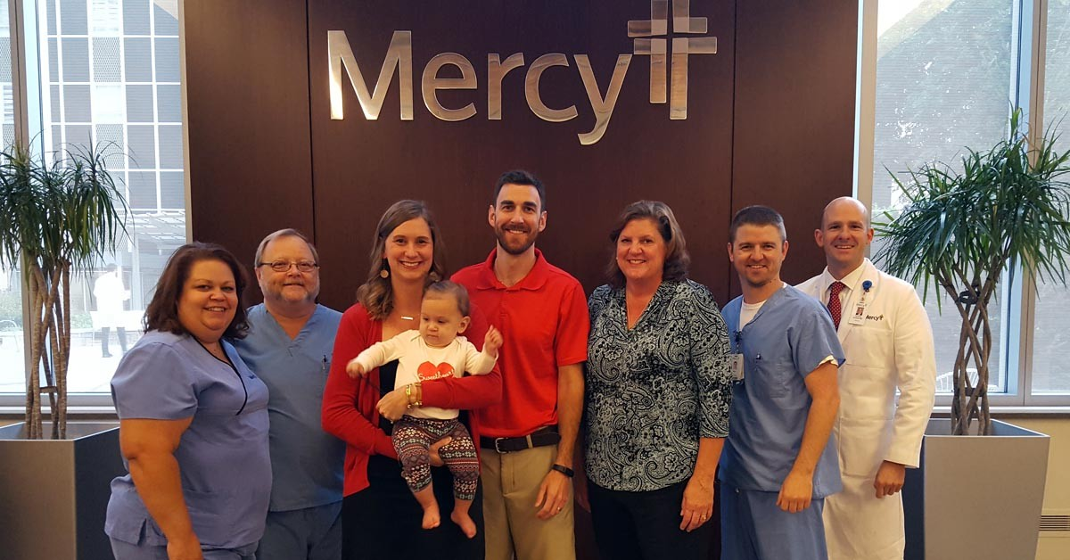 Jessica and her family pose with the team that helped save her life. Left to right: Terri Sheets, RN, Dennis Becker, cath lab tech, Jessica Grib and Amelia, Kevin Grib, Patty Gilham (Jessica's mom), Kyle Hoffman, RN, and Dr. Tim Schloss.