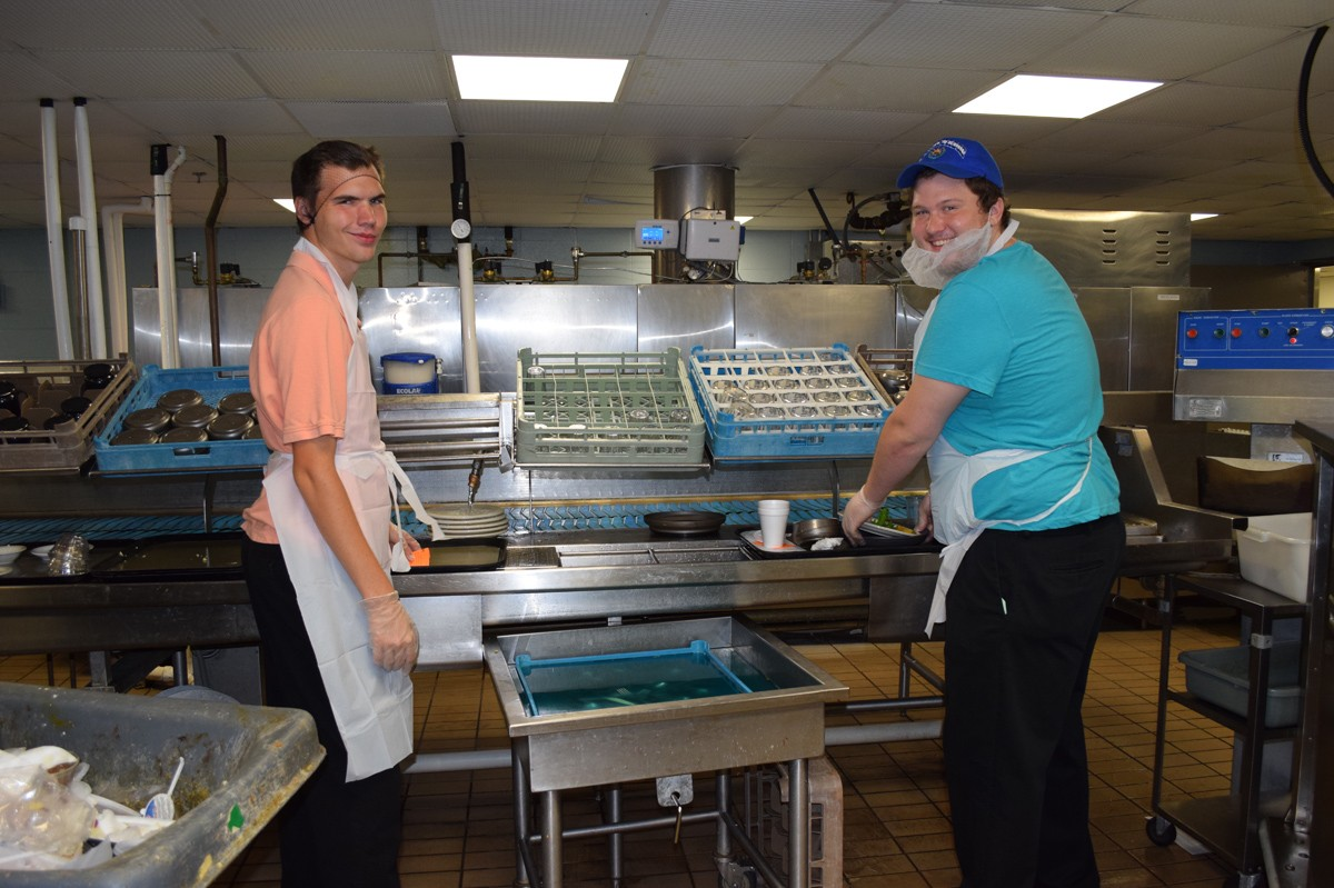 Intern John Michael Haas likes working in the dish room where he can be active and sing! Here, he's working with volunteer Asher Tillman.