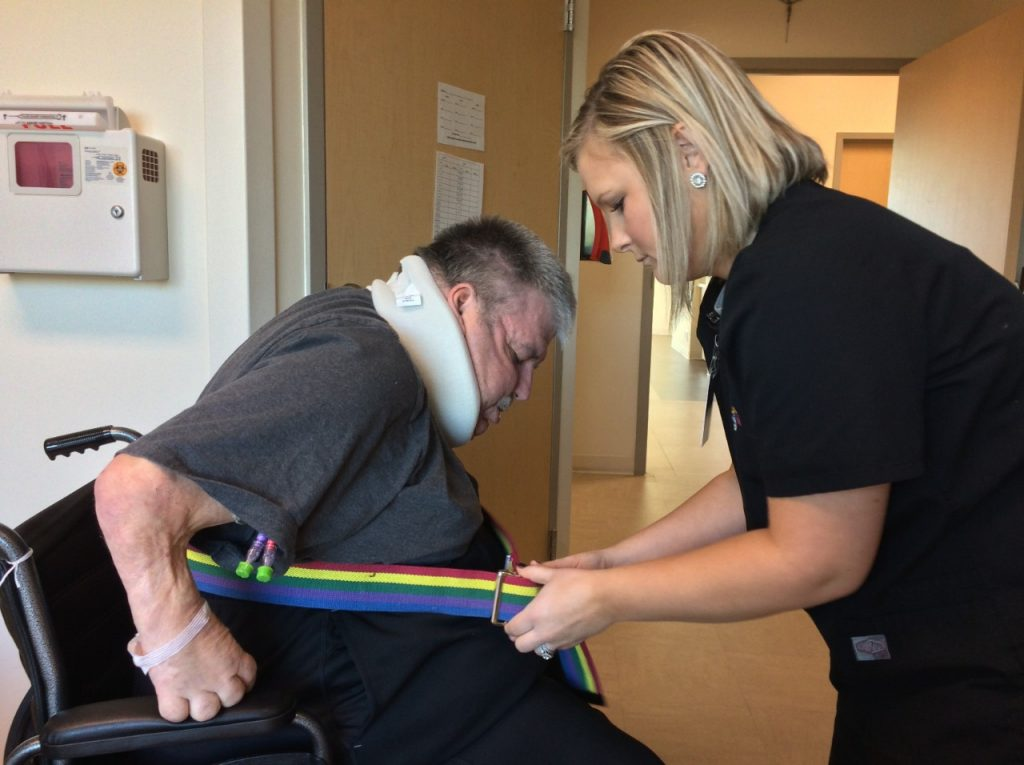 Patient Greg Redfern receives help getting up from a wheelchair. After a stay at Mercy Rehabilitation Hospital Springfield, he is once again able to walk.