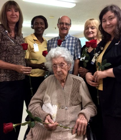 Friends presented Hazel Burt with 10 roses (one to represent each decade of her life) in observance of her 100th birthday.   Pictured are: Becky Davied, Mercy Home Health and Hospice director; LaShawn Noel, Mercy Hospice social worker and volunteer coordinator; Marty Dewitt, pastor of First Missionary Baptist, Uniontown; Wanda Ogle, Mercy RN; and Melissa George, Mercy Hospice chaplain.
