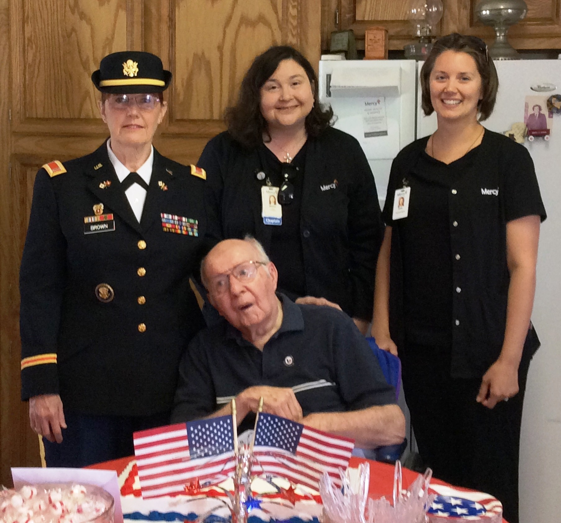 CW5(R) U.S. Army Faye Brown, Mercy Hospice volunteer; Melissa George, Mercy Hospice Chaplain; Kerry Wunderly, Mercy R.N.; honored Specialist Jackie Plain (center) for his military service.