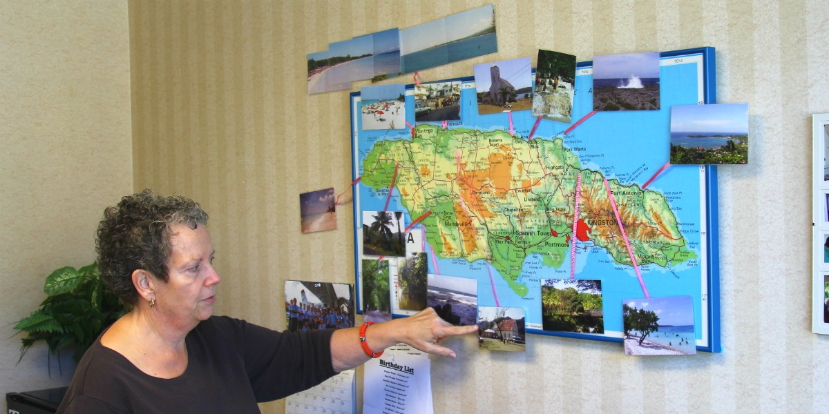 Karent Fenstermacher shows a map and photo display in her office depicting her medical mission trips to Jamaica.