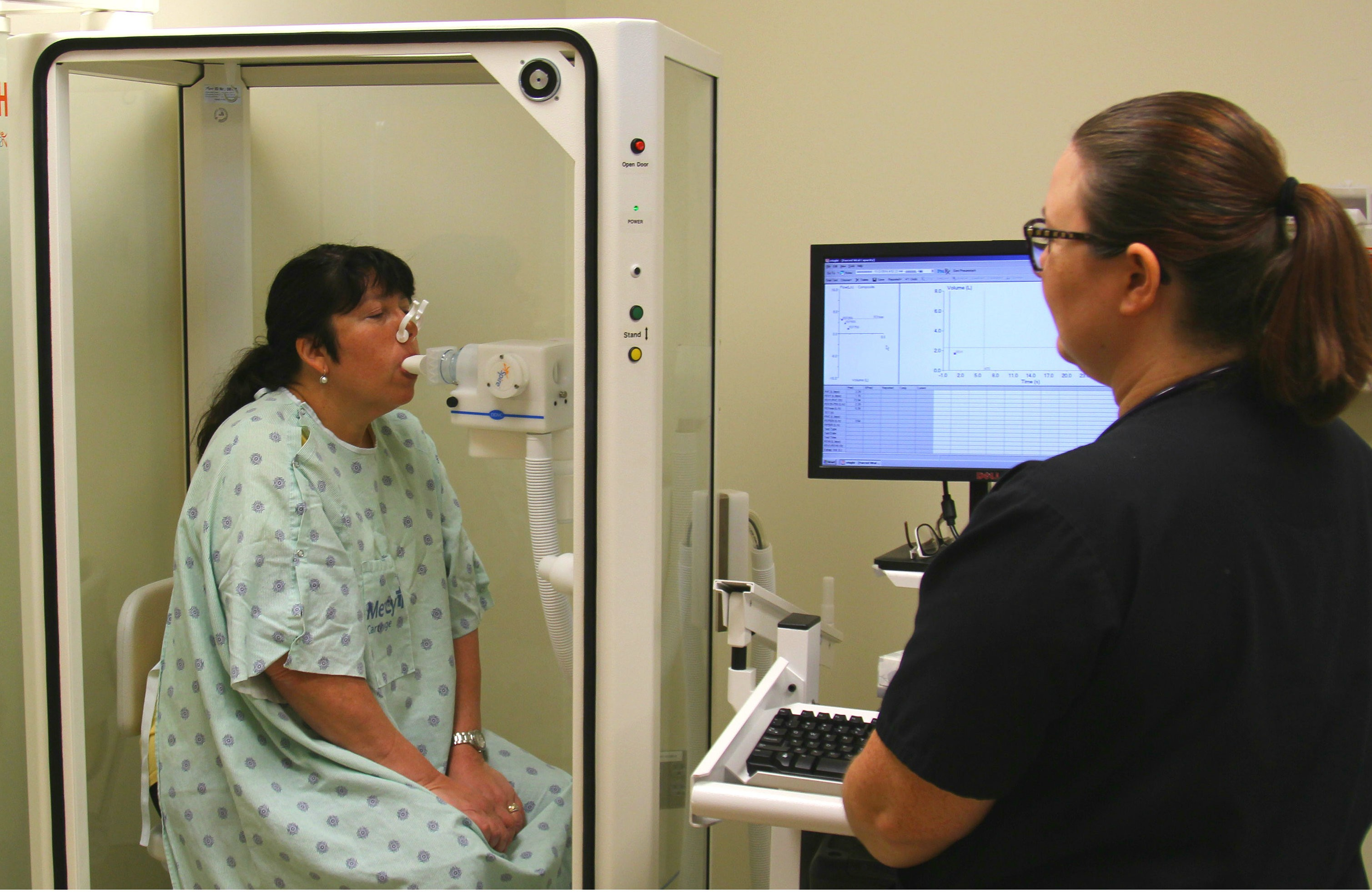 Sara Dobkins, a respiratory care practitioner, performs a pulmonary function test on a patient using a plethysmograph at Mercy Carthage.