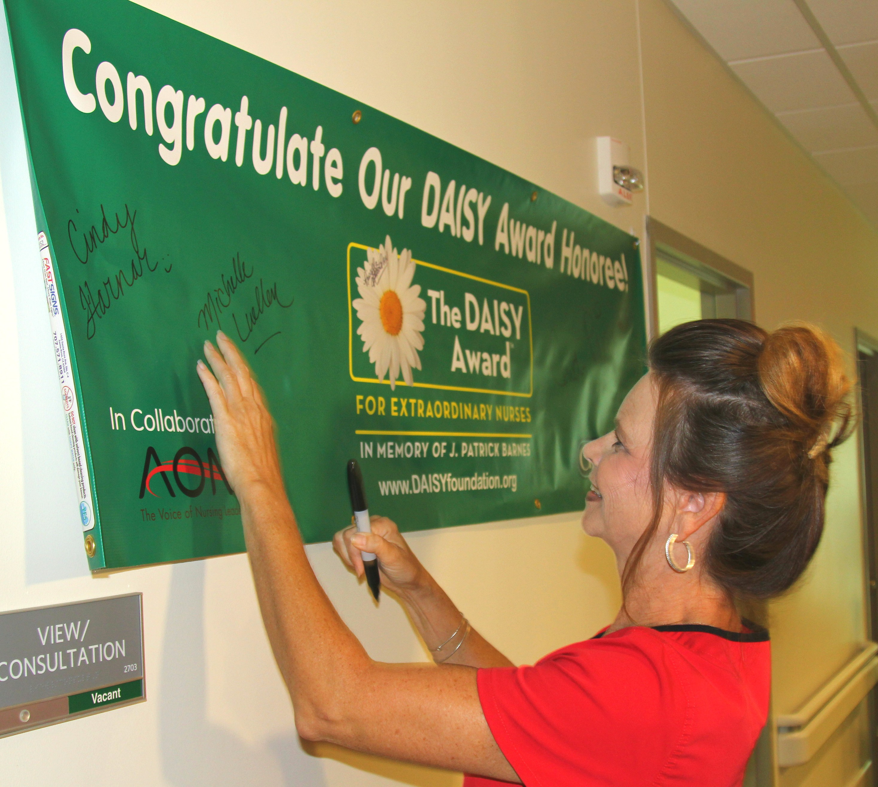 Michelle Luellen, a registered nurse at Mercy Clinic Oncology and Hematology – Joplin, signs the DAISY Award banner at Mercy Cancer Center.