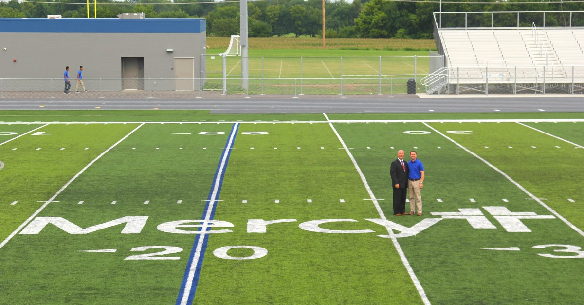 Scott Watson (left), administrator for Mercy Hospital Carthage, and Dr. Jonathan Haffner of Mercy Clinic Family Medicine in Carthage are dwarfed by the Mercy logo on Mercy Field at Carthage High School. Mercy Hospital Carthage donated $250,000 to help with construction of the complex.