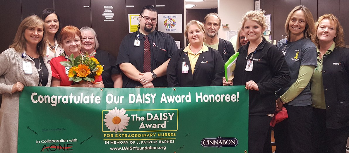 Surrounded by several co-wokers, Nancy Elias (with daisy bouquet) is the latest DAISY Award winner at Mercy Hospital Jefferson.
