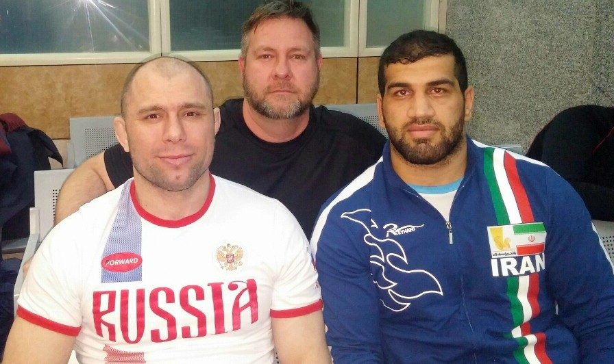 Ryan Palmer is with Khetag Gazyumov, left, a retired Russian and Azerbaijani wrestler who won 12 world and Olympic medals, and Jaber Sadeghzadeh, a back-up Iranian heavyweight for the tournament.