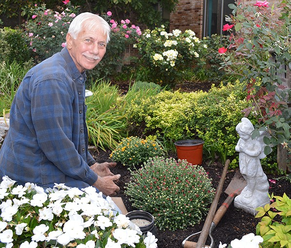 Hospice volunteer Ron Olsen prepares the memorial garden prior to the annual celebration and dedication.