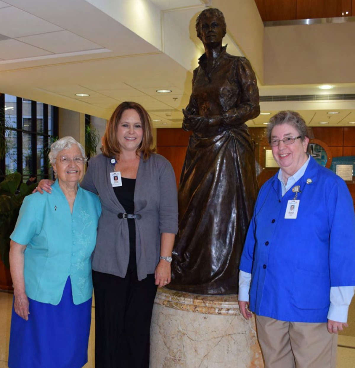 Shown at right: (Center) Jennifer Battagler, director of volunteer services, joins Sister Carmen Gonzalez (left) and Sister Margaret Andrews at the statue of Catherine McAuley in the lobby of Mercy Hospital Springfield.