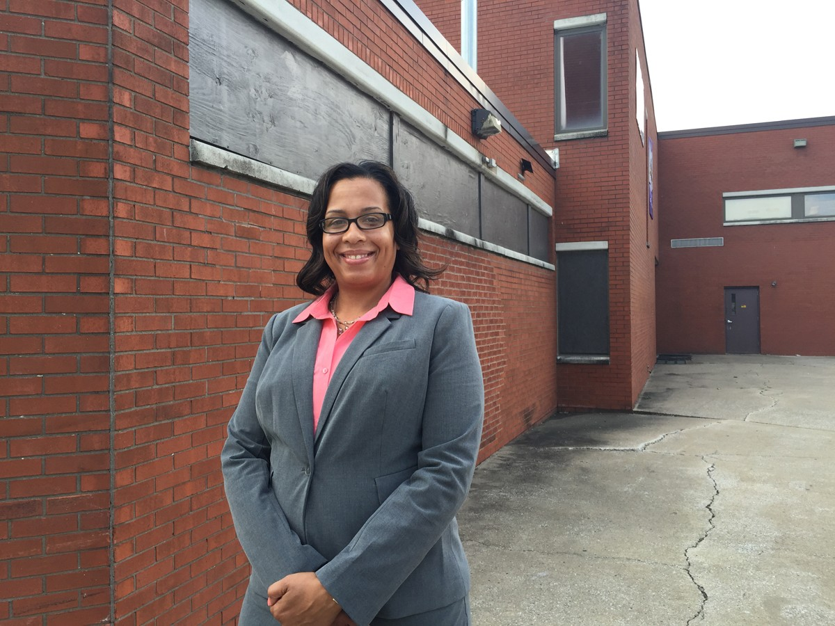 Theresa Densmore, MBA, stands in front of the now closed AM Jackson Elementary School in East St. Louis, Illinois, where she first discovered her love for numbers as a fourth-grade student who won a statewide mathematics competition.