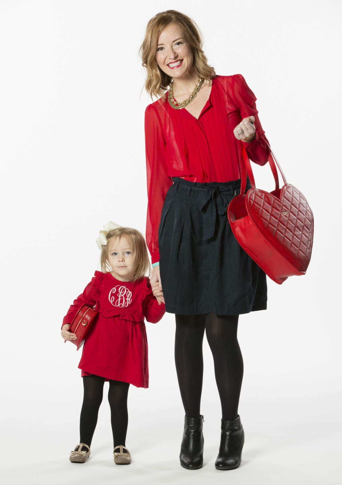 Wear Red for Women committee member, Megan Broderick and daughter, Charlee, model purses that will be available for auction at Ada's Wear Red for Women event on Friday, February 17.